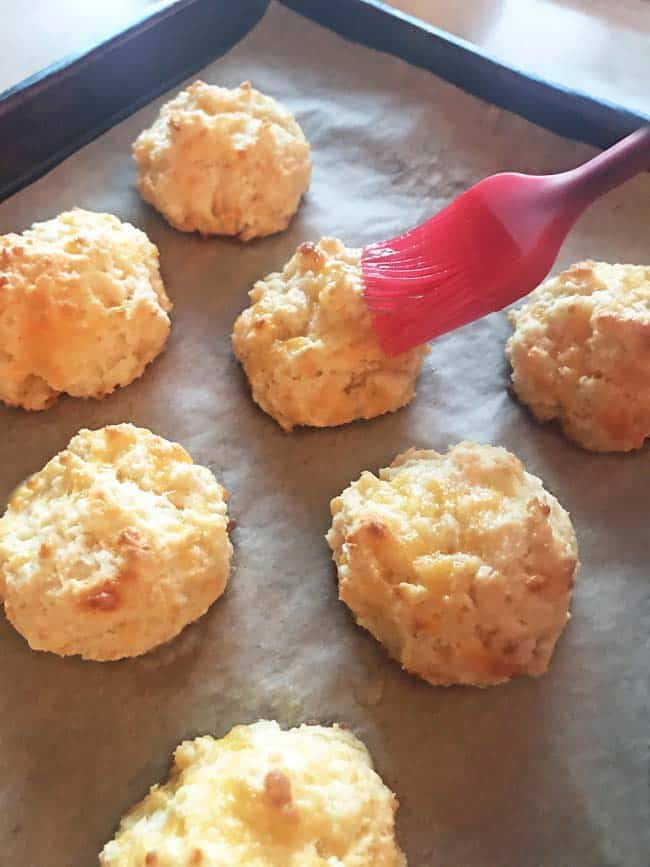 Brush cheddar drop biscuits with butter