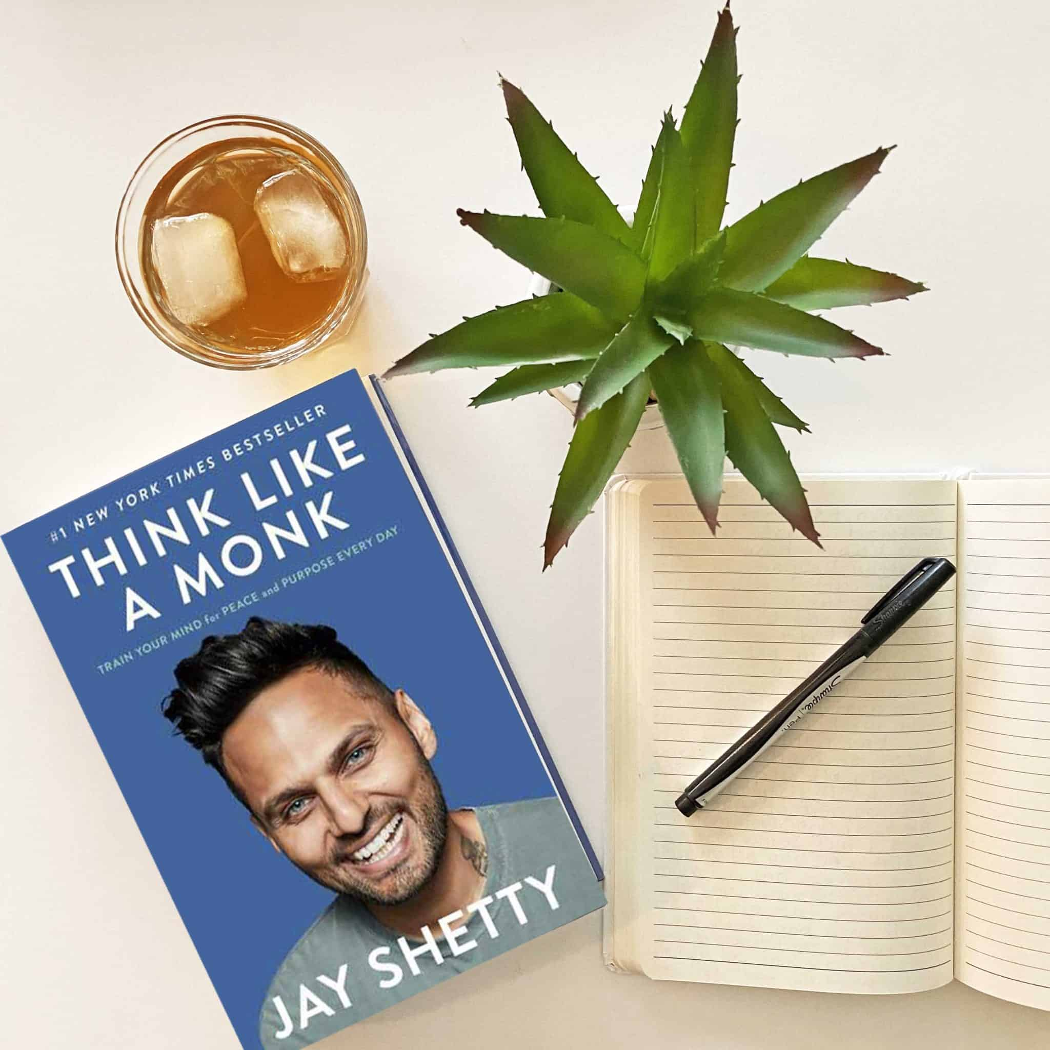 Think like a monk book by Jay Shetty shown with a plant, a journal, a pen and a glass of iced tea