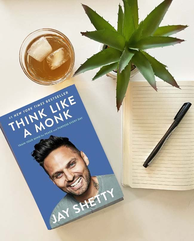 The book Think Like a Monk, a glass of iced tea, a succulent plant, a journal and a pen